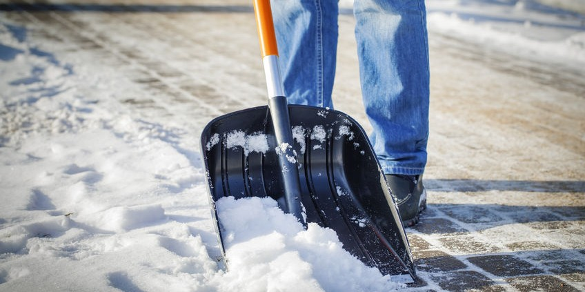 25868143 - man with snow shovel cleans sidewalks in winter