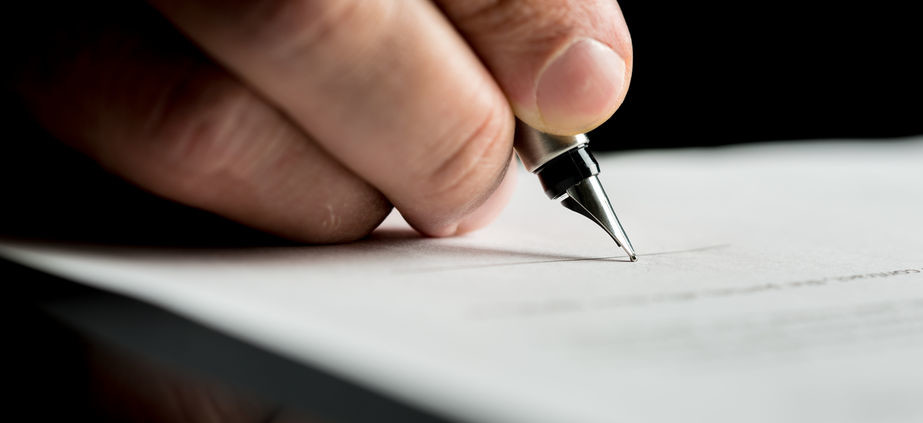 Macro shot of a hand of a businessman signing or writing a docum